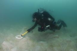 Diver undertakes handheld magnetometer survey over a sandy area.