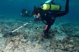 Diver undertaking survey with handheld magnetometer.