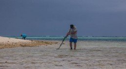 John Mullen surveys the shallows by Observatory Cay, Kenn Reefs, with a metal detector. Image: Julia Sumerling for Silentworld Foundation, 2017.