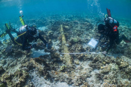 Maritime archaeologists Irini Malliaros and James Hunter record one of the two anchors found on Boot Reef.